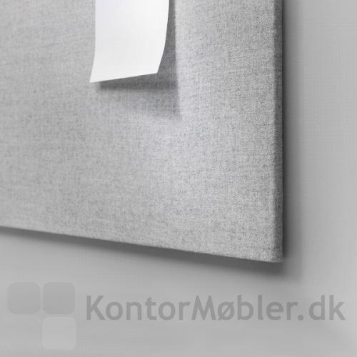 Opslagstavle uden ramme set fra siden i et grå tonet arbejdsmiljø