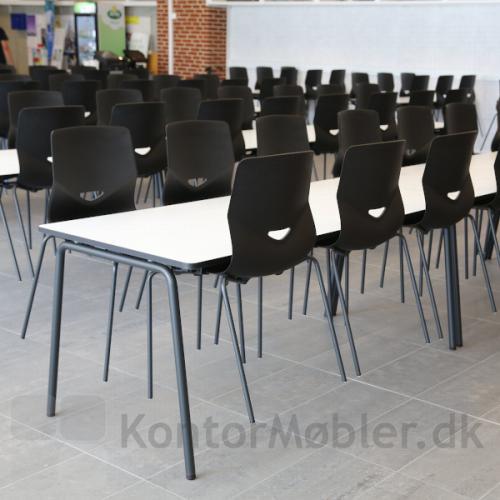 Four Real 74 møde/kantinebord ses her med varm grå pulverlakeret stel samt sorte Four Sure 44 stole med praktisk gribehul